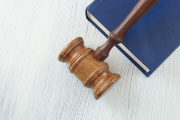 Judge wooden gavel and legal book on white table with space for text