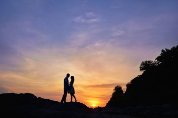Silhouette of a couple in love on a sunset tropical background.