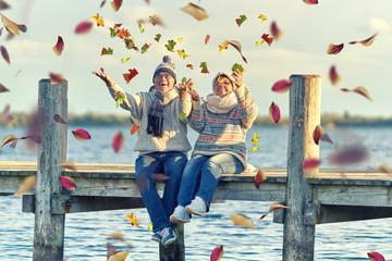 Herbst, Senioren werfen buntes Laub in die Luft