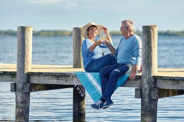 Picknick am See, mit Wein anstoßen, Seniorenpaar
