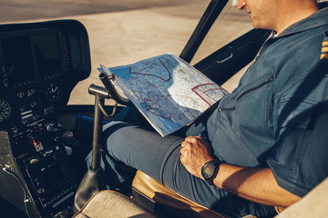 Helicopter pilot reading map.