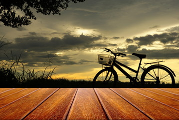 perspective wood table with backgound of bicycle sillouette at sunset nature background