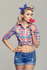 woman eating heart shape lollipop, dressed in pin-up style