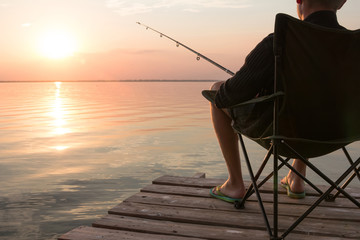 fisherman with rod over the lake at sunset