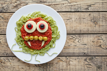 Green spaghetti pasta creative spooky halloween vegetarian food vampire monster with smile, fake blood tomato sauce and funny big mozzarella eyeballs holiday decoration kid party meal on vintage table