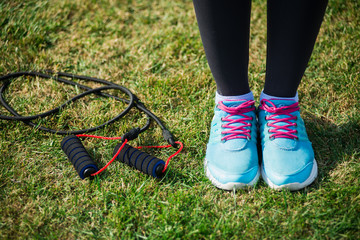 sneakers and variegated skipping rope on bright green grass background. Jumping rope on open air