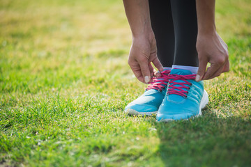 Woman preparing before run putting on running shoes