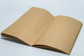 Opened Brown plain notebook with white background and selective focus