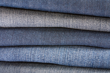 Closeup of stack of different shades of blue denim for background