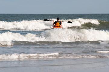 Man having fun kayaking in the ocean waves