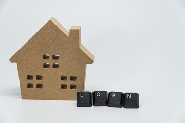 Wooden house toy and LOAN word from keyboard with white background and selective focus