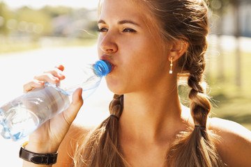 Young beautiful sports girl drinks drinking water during morning