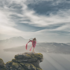 Girl in pink dress up on a rock