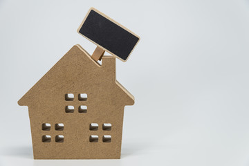 Wooden house toy and small black board with white background and selective focus