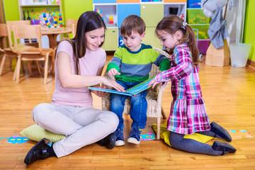 Kids reading book with their kindergarten teacher