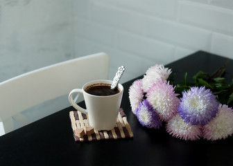 A cup of hot coffee. Bouquet of asters on the table. Romantic breakfast.