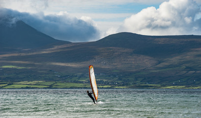 Wind surfing on the west coast of Ireland with wild rugged natural landscape in the background