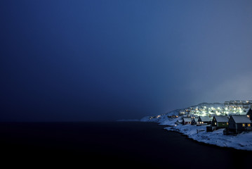 Illuminated houses by sea against clear sky