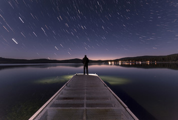 Rear view of man standing on jetty and looking at star rail