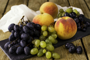 a bunch of green and black grapes and peaches on a wooden backgr