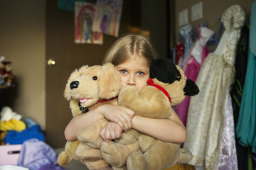 Girl holding stuffed toys in bedroom at home