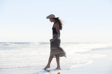 Woman in sun hat walking in sea against sky on sunny day