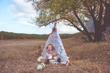 Child girl in decorative hovel on the nature