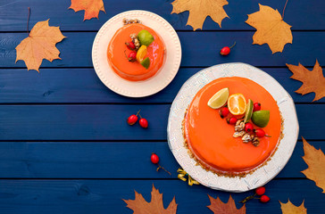 Two cakes decorated with orange mirror glaze on blue wooden background. Free place for text. Autumn pie, autumn still life concept.