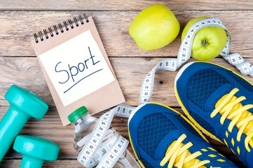 "Sport shoes, apples, bottle of water, measuring tape, dumbbells and words ""Sport"" written on paper note. Sport equipment. Sports  lifestyle and healthy food concept. Copy space"