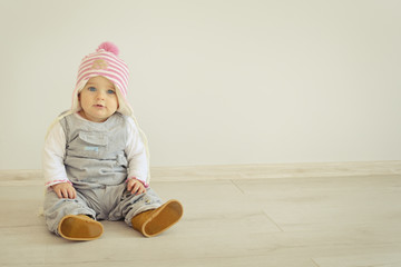 Baby on floor. A cute little girl is looking into the camera and is wearing a pink knitted hat. Blue eyes kid. Parenting or love concept.