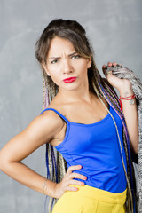 Woman portrait with colorful dreadlocks is a studio, hippie style. Beautiful modern girl has makeup and wears fashionable clothes.