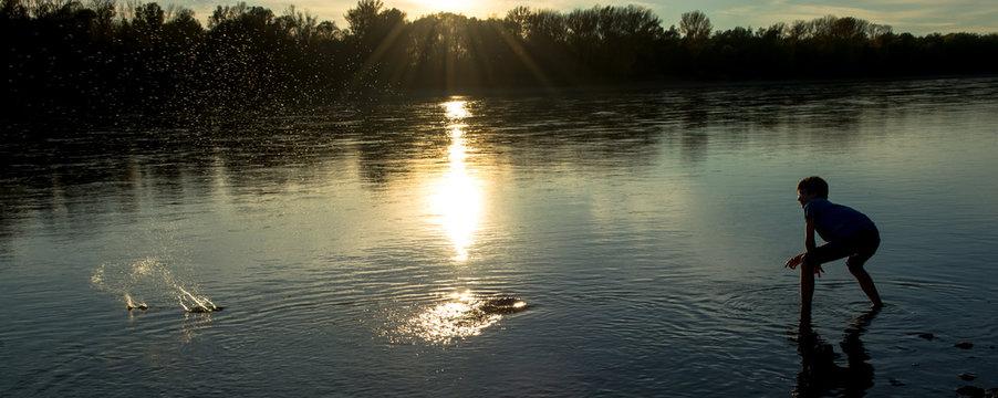 Bub wirft Steine in Fluss bei Sonnenuntergang