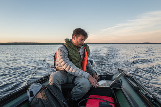 Man is seating in the boat and working with laptop
