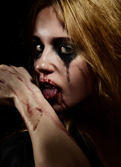 crazy blooded girl with smeared cosmetics licking blood