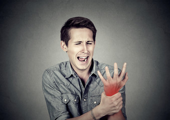 man holding his painful wrist