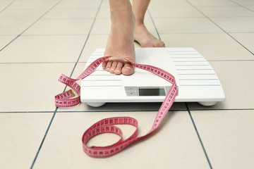 Female leg stepping on floor scales with centimeter