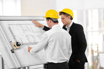 Two male engineers working with new project on drawing board on blurred office background