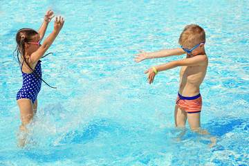 Little boy and girl playing in swimming pool