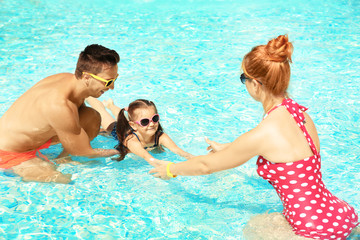 Parents teaching little daughter to swim