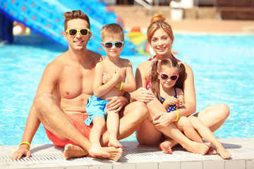 Happy family near swimming pool at water park