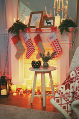 Stool with Christmas decor near fireplace