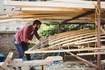 Man preparing wooden boat frame