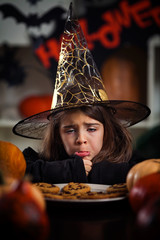Cute little girl in a Halloween costume is ready for Trick or Treat. She is making scary and funny faces pretending to be a witch.