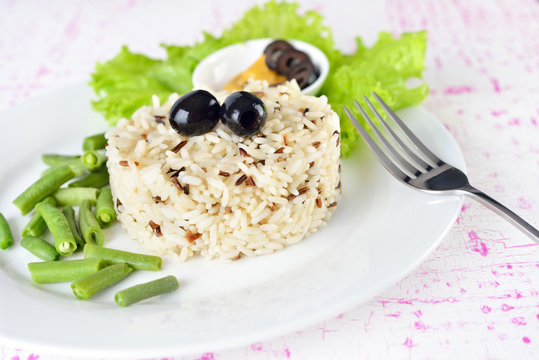 Bowl of cooked mixed wild Rice. Plate Served with salad and green bean vegetable.