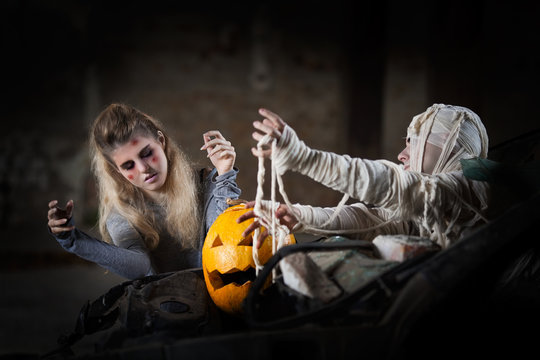 Zombie and Mummy attack on a Jack O' Lantern from an old broken car in a creepy dark haunted house.