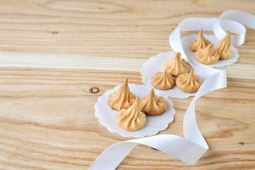 Vanilla meringue cookies on wooden background with copy space. Cakes with white ribbon.