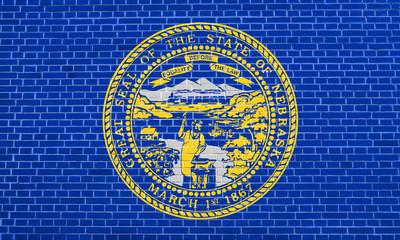 Flag of Nebraska on brick wall texture background