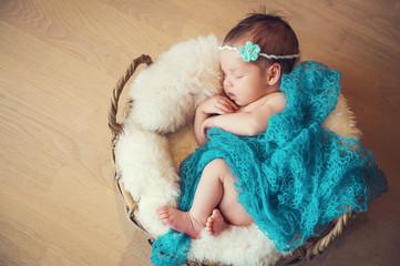 Sleeping newborn baby in a basket
