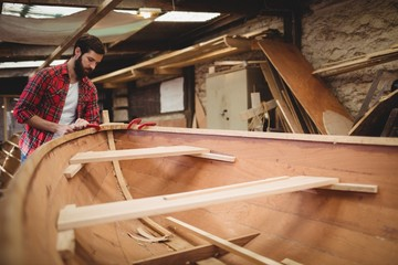 Man preparing wooden boat frame