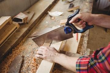 Man cutting a wooden plank